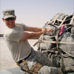 SPC Grannis tightens the straps on palettized cargo in Iraq, which will be loaded onto a cargo plane.